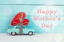 Mothers Day Background With Miniature Blue Toy Car Carrying A He