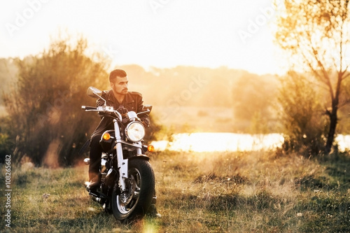 young brutal man in a black jacket and glasses sits near a motorcycle Canvas