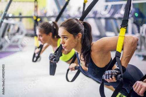 Fotobehang Fitness Women training arms with trx fitness straps in the gym doing push ups train upper body chest shoulders pecs triceps.