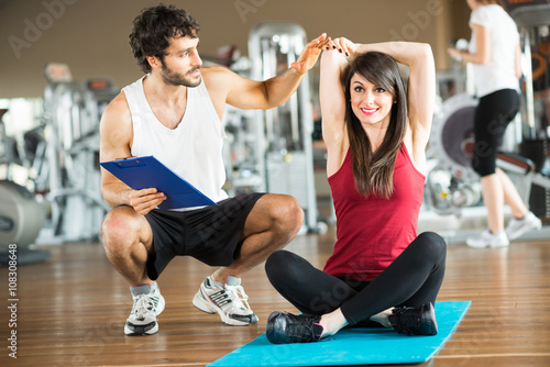 Woman doing stretching while a personal trainer watches her