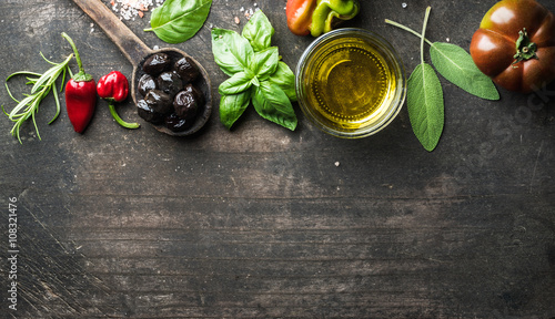 Food background with vegetables, herbs and condiment. Greek black olives, fresh basil, sage, rosemary, tomato, peppers, oil on dark rustic wooden background.