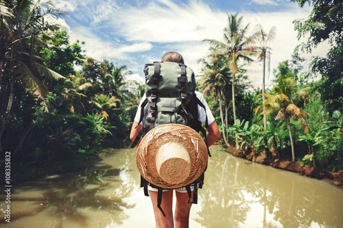 Fotografia  Traveler woman with backpack standing near big tropical river at sunny day