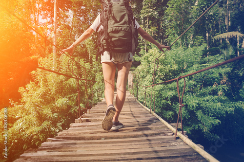 фотографія  Young woman with backpack balancing across hanging bridge in tropical forest (in