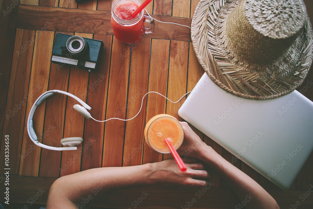 Fototapety, obrazy: Freelance woman and the table with fresh juice, laptop, film camera, mobile phone and headphones (intentional vintage color)