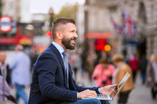 Photo  Hipster manager working on laptop on sunny Piccadilly Circus, Lo
