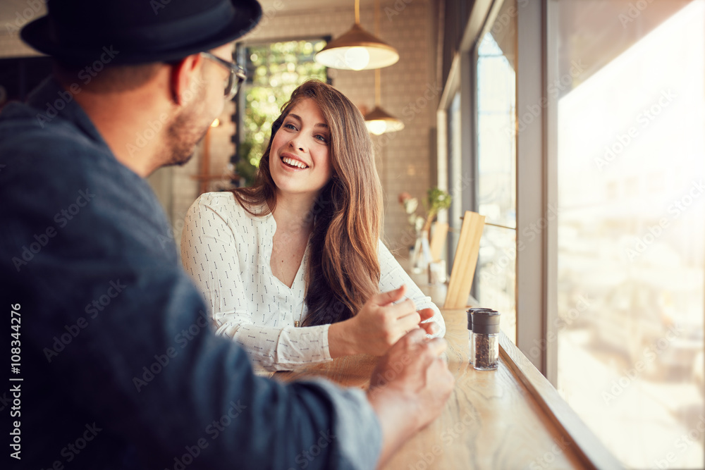 Fototapeta Smiling young woman at cafe with her boyfriend