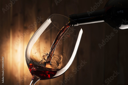 Obraz na plátně  glass with red wine on wooden background