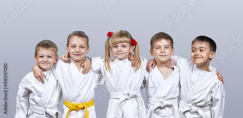Foto op Aluminium Vechtsport On a gray background little athletes in karategi