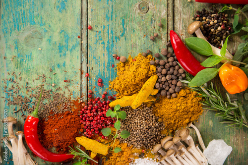 Various colorful spices on wooden table Poster