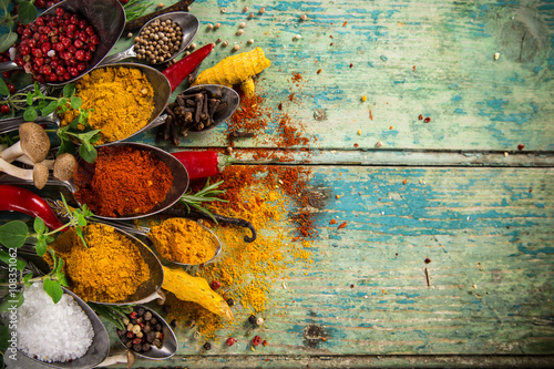 Various colorful spices on wooden table Wallpaper Mural
