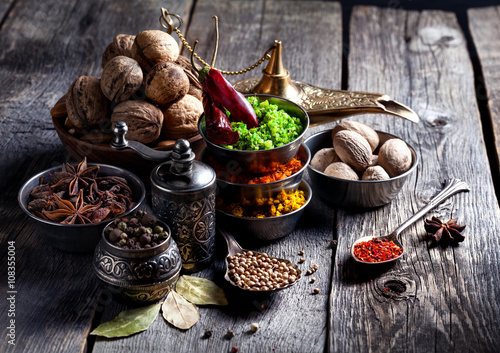 Spices and nuts at wooden table Tablou Canvas