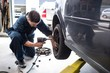 Mechanic changing car wheel with pneumatic wrench
