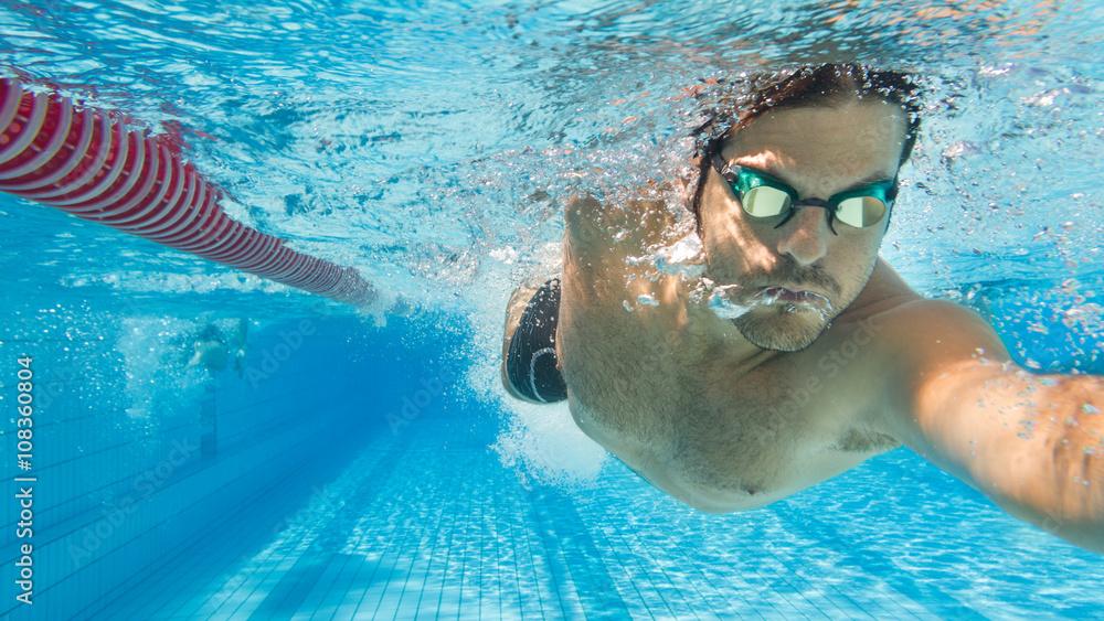 Photo  Mann krault im Freibad auf Schwimmbahn - Unterwasseraufnahme