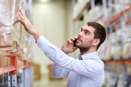 Foto  serious man calling on smartphone at warehouse