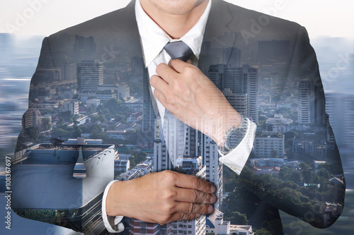 Photographie  Businessman held necktie dress to look good and city in a foggy morning as Readiness concept