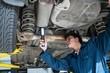 Mechanic examining car using flashlight