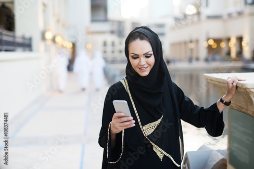 Arabian woman typing on smart phone and smiling. Wallpaper Mural