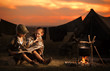 Two of children sitting around the campfire travelers