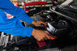 Mechanic checking and fixing a broken car in car service garage