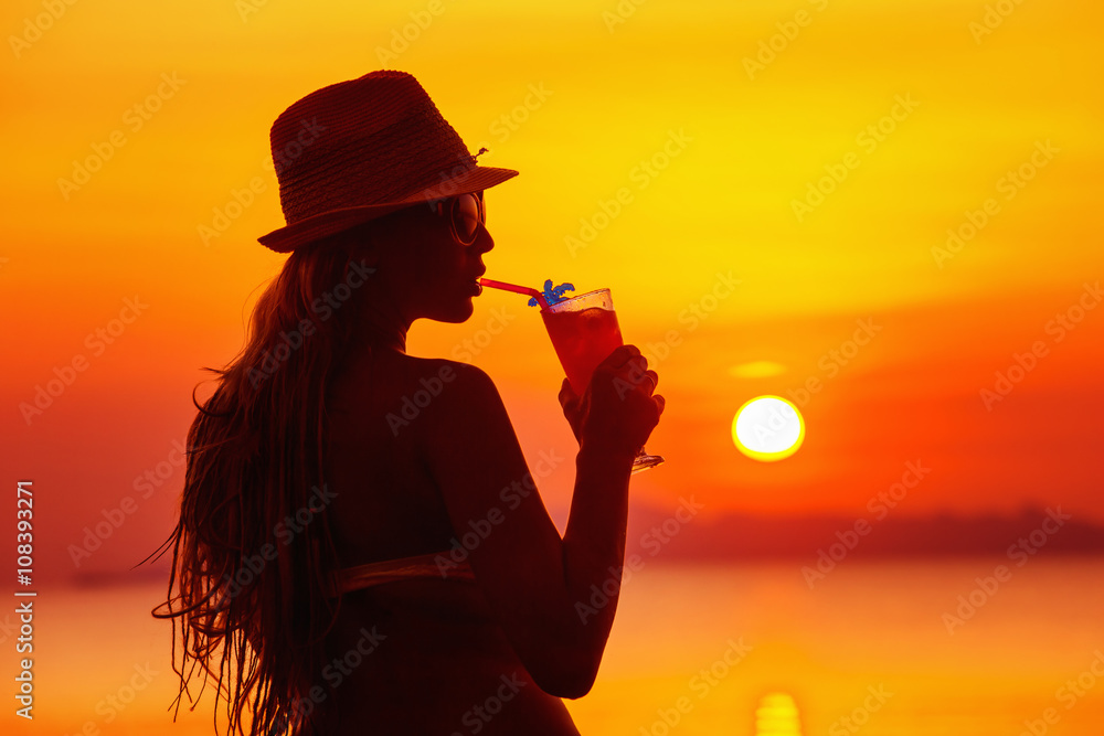 Fototapeta Closeup portrait of woman in hat with cocktail at tropical sunset