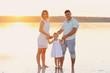 Мама, папа и маленькая дочь стоят в море