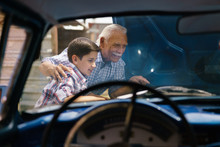 Boy With Grandpa Looking Car Engine Of Senior Man