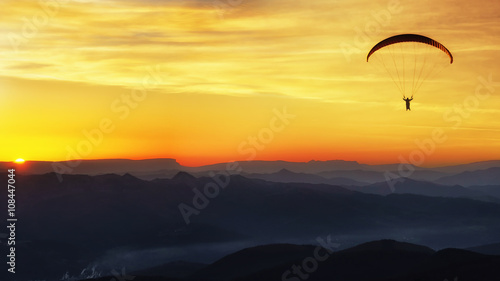 Canvas Prints Cuban Red Paraglide silhouette over mountains at sunset