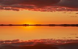 Orange and red sky after the sunset at a lake in Finland. Symmetrical reflection of clouds in the still water.