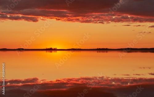 Foto op Canvas Baksteen Orange and red sky after the sunset at a lake in Finland. Symmetrical reflection of clouds in the still water.