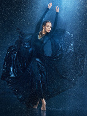 FototapetaThe young beautiful modern dancer dancing under water drops