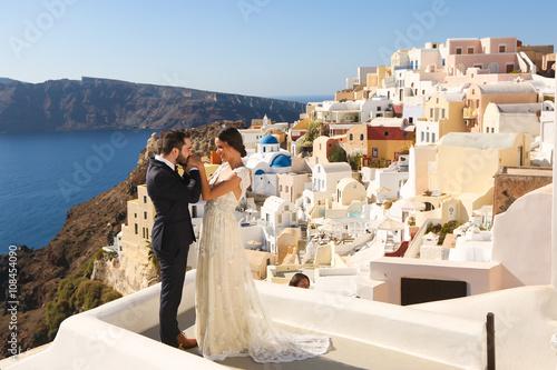 Fototapeta bride and groom posing in Santorini obraz