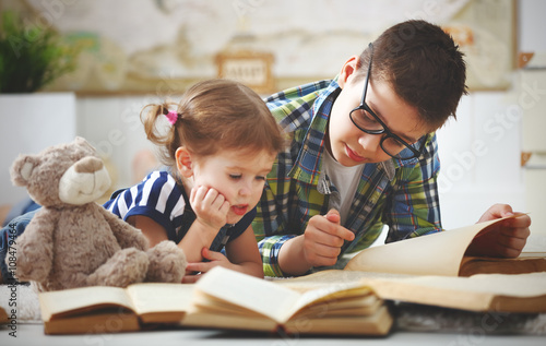 children brother and sister, boy and girl reading a book Canvas Print