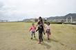 芝生の上を歩く家族 アジア人 母と子供達
