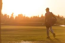 Golfer  Walking And Carrying Golf  Bag At Beautiful Sunset