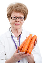 Old Age Female Doctor Holding Red Fresh Carrots In Hands, Isolated On White Screen