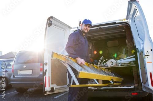 Portrait of handyman loading a ladder