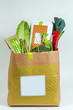 Various fresh greens, vegetables and white box in paper bag