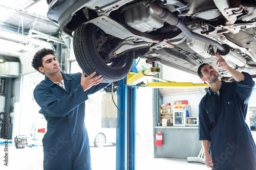 Mechanic fixing a wheel while a colleague examining car