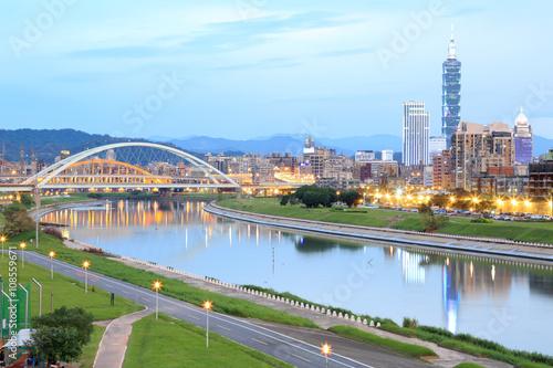Fototapeta premium Nocna sceneria Taipei City z pięknymi odbiciami drapaczy chmur i mostów na gładkiej wodzie nad rzeką o zmierzchu ~ Pejzaż Tajpej 101, rzeka Keelung, dzielnica Xinyi i centrum o zmierzchu