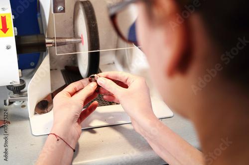 Pracownia jubilerska, ręczne tworzenie biżuterii. Jubiler poleruje biżuterię na polerce jubilerskiej.