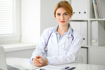 Female doctor sitting at the desk near window