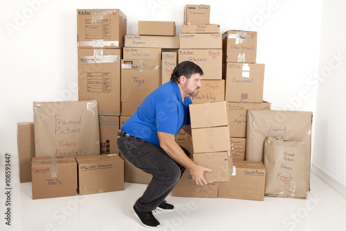 Fotografie, Obraz  Man lifting and holding moving boxes