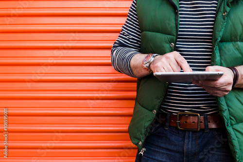 Young Man Using A Tablet In Front Of An Orange Garage Door Dressed