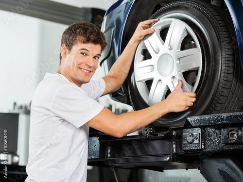 Fényképezés Happy Mechanic Fixing Hubcap To Car Tire