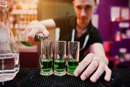 Photo Barman preparing green mexican cocktail drink at the bar