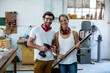 Male and female carpenters standing together with wooden plank a
