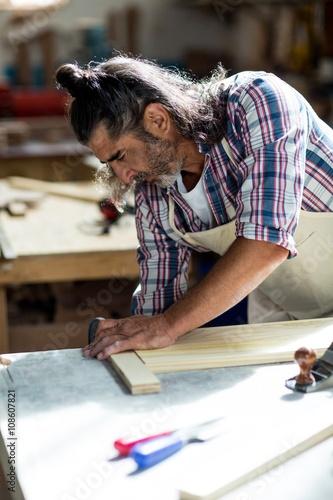 Male carpenter measuring wooden plank