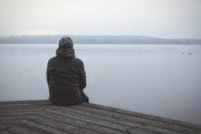 Einsamer Mann Sitzt Auf Steg Am See Oder Fluss / Lonesome Huy At The Lake
