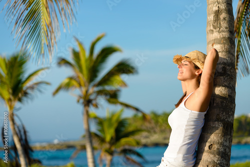 Woman on caribbean travel relaxing and resting under tropical palm trees Canvas Print