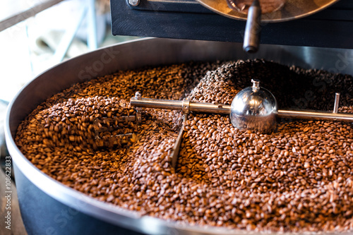 Fotografija Freshly roasted coffee beans from a large roaster in the cooling cylinder